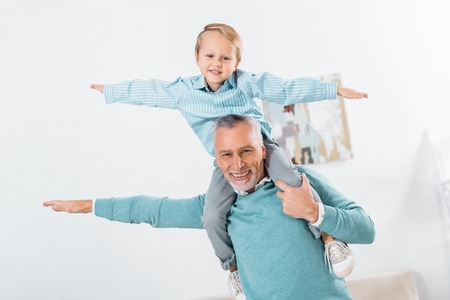 happy kid sitting on grandfather shoulders and imitating plane at home Stock Photo
