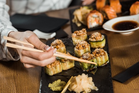 Partial view of woman eating sushi rolls with chopsticks Stockfoto