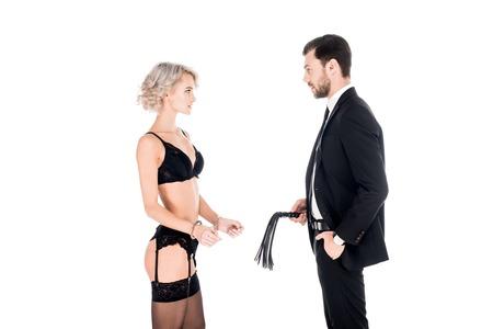 Bel homme tenant le fouet tandis que la femme debout en lingerie et menottes isolées sur blanc