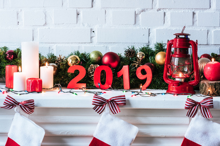 2019 year sign with Christmas wreath, candles and socks Stock Photo