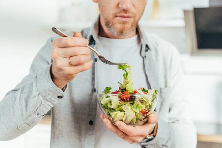 cropped shot of man eating vegetable salad at home
