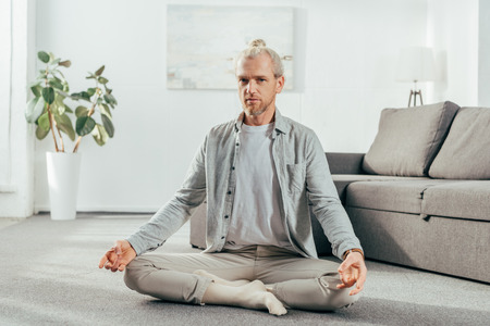 flexible adult man meditating in lotus position and looking at camera at home