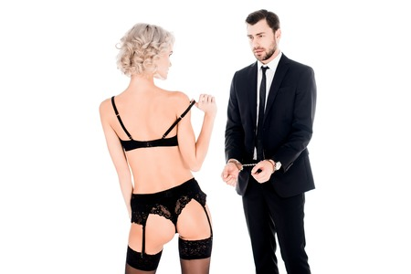 Couple of young adults looking at each other while man is in handcuffs and woman in lingerie isolated on white