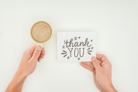 hands holding thank you lettering on white postcard and coffee isolated on white background