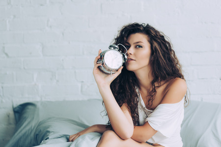 cheerful curly young woman sitting on bed with alarm clock at home