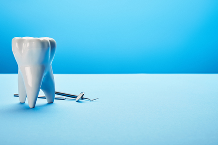 close up view of sterile dental mirror, probe and tooth model arranged on blue backdrop