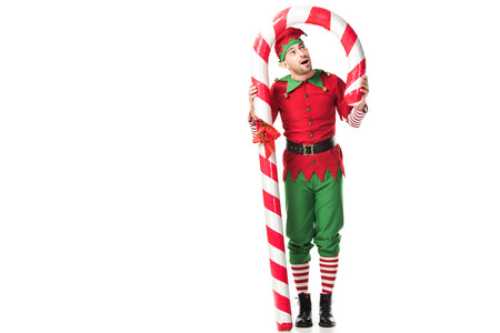 surprised man in christmas elf costume standing under big candy cane isolated on white Stockfoto