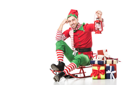 man in christmas elf costume sitting on sleigh near pile of presents and holding red lantern isolated on white