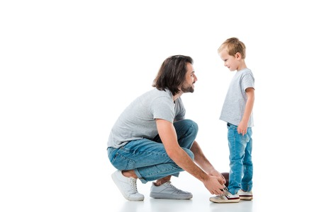 Caring father helping his son to tie shoelace isolated on white