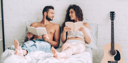 happy young couple sitting with books and looking at each other on bed at home