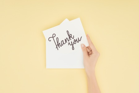 cropped person holding white postcard with thank you lettering isolated on yellow background Stockfoto