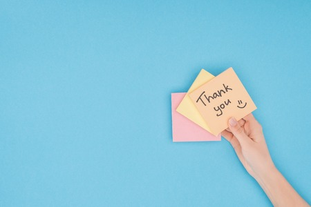cropped person holding colorful sticky notes with thank you lettering isolated on blue background