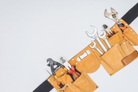 Vue de dessus de la ceinture de la trousse à outils avec divers instruments de réparateur isolated on white