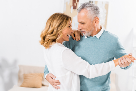 selective focus of mature couple looking at each other while dancing at home Stockfoto