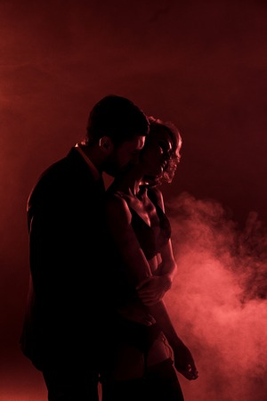 Man tenderly hugging beautiful woman and kissing her in neck on red smoke background Stock Photo
