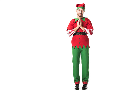 man in christmas elf costume holding palms together as please gesture and having hopeful expression isolated on white
