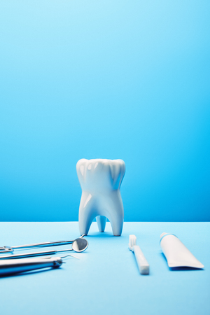 close up view of white tooth model, toothbrush, toothpaste and stainless dental instruments on blue backdrop Banque d'images - 112386647