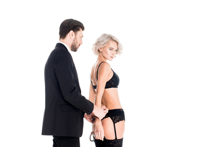Handsome man handcuffed seductive woman in lingerie isolated on white Imagens
