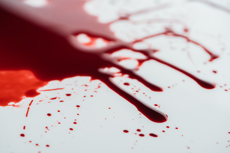 close-up shot of flowing blood droplets on white surface Stock Photo