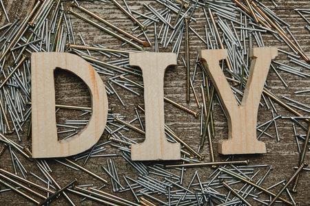 Top view of wooden diy sign and various nails tools on wooden table