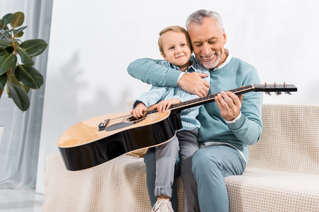 selective focus of laughing grandfather playing with grandson on knees playing on acoustic guitar at home Standard-Bild