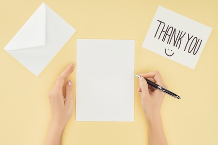 cropped person holding pen, blank sheet, postcard with thank you lettering and smartpone isolated on yellow background