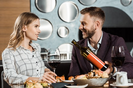 Man offering his beautiful girlfriend wine while they having dinner in restaurant