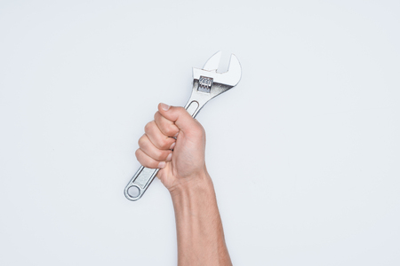 cropped shot of man holding adjustable wrench isolated on white