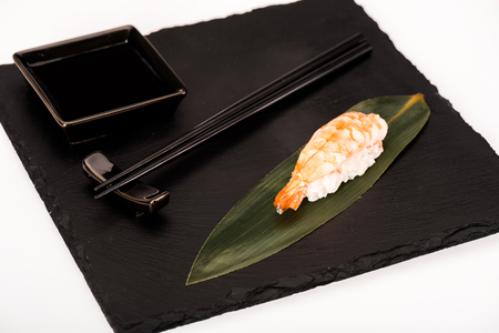 Nigiri sushi with shrimp served with chopsticks and soy sauce on black slate