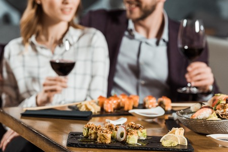 Partial view of couple eating sushi and drinking wine while having date in restaurant