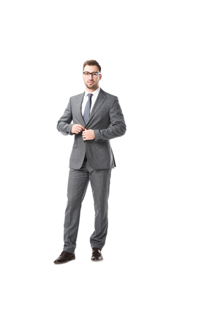 adult businessman in glasses fastening jacket isolated on white