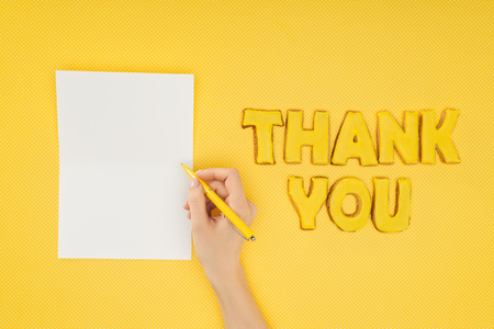 cropped person holding pen above blank sheet and thank you lettering in cookies isolated on yellow background