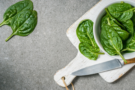 Top veiw of organic and green spinach leaves in bowl on white cutting board