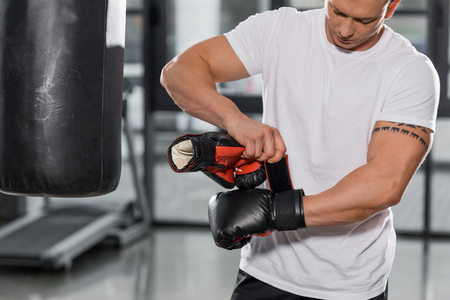 handsome tattooed boxer wearing boxing gloves in gym