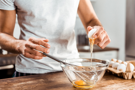 close-up partial view of young man preparing omelette for breakfast