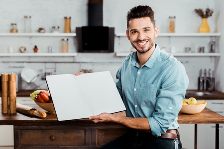 handsome young man holding blank cookbook and smiling at camera in kitchen