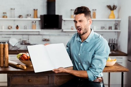 handsome young man holding blank cookbook and winking at camera in kitchen