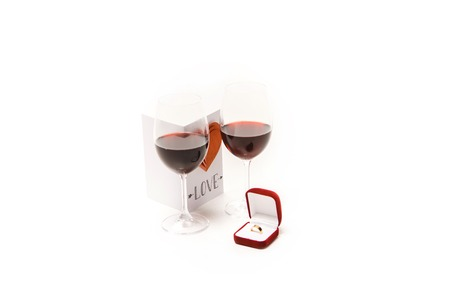 Two glasses with red wine, lovely postcard with heart and ring box isolated on white