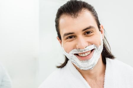Man with shaving foam on beard smiling in bathroom