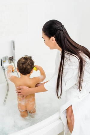 Mother with long hair washing son in white bathroom