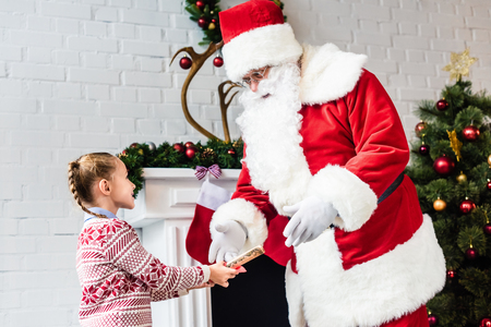 adorable little child giving rolled wishlist to santa claus Stock Photo