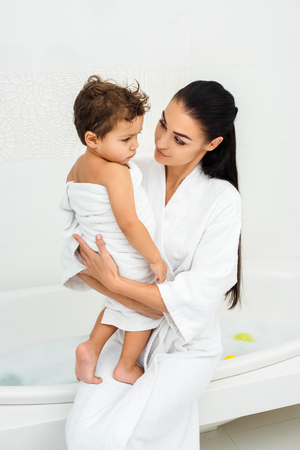 Mommy looking at toddler son in towel in bathroom