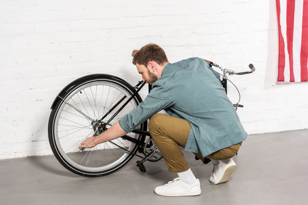 side view of young man repairing bicycle by adjustable spanner Stock Photo