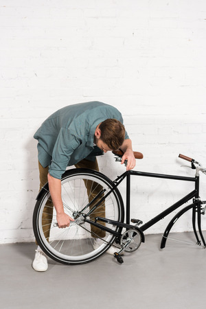 young man repairing bicycle by adjustable spanner 免版税图像