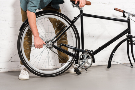 cropped image of young man repairing bicycle by adjustable spanner Stock fotó