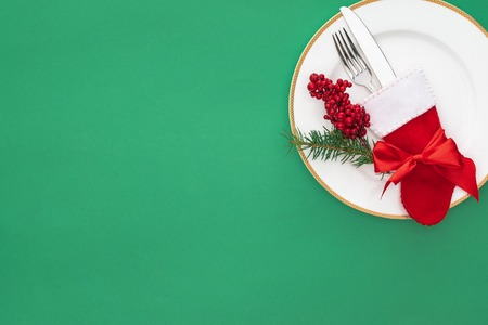 elevated view of red berries, evergreen tree branch and fork with knife in christmas sock on plate isolated on green