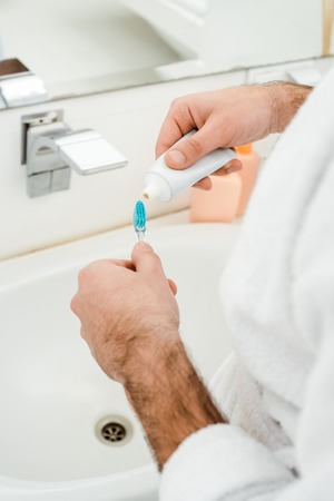 cropped view of male hands adding toothpaste on toothbrush in bathroom