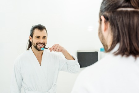 handsome adult man in white bathrobe brushing teeth in bathroom