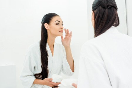 woman with perfect skin applying face cream in bathroom