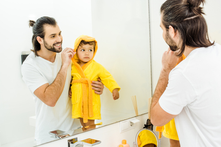 smiling father holding cute toddler son in yellow bathrobe in bathroom